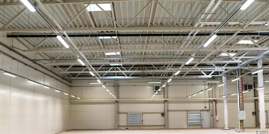 Emergency lighting with dual-function fixtures in a storage area
